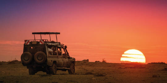 Safari Vehicle Driving Into Sunrise at Masai Mara, Kenya